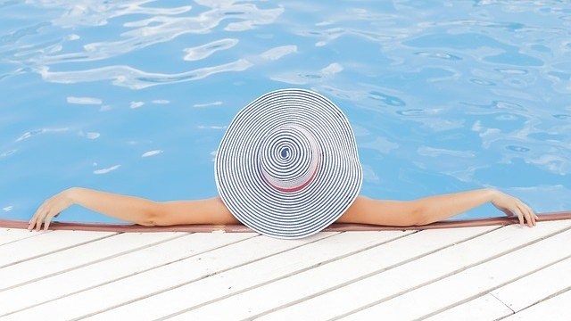woman cooling off in a pool on a hot summer day