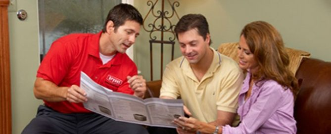 HVAC technician showing homeowners their options for air conditioners